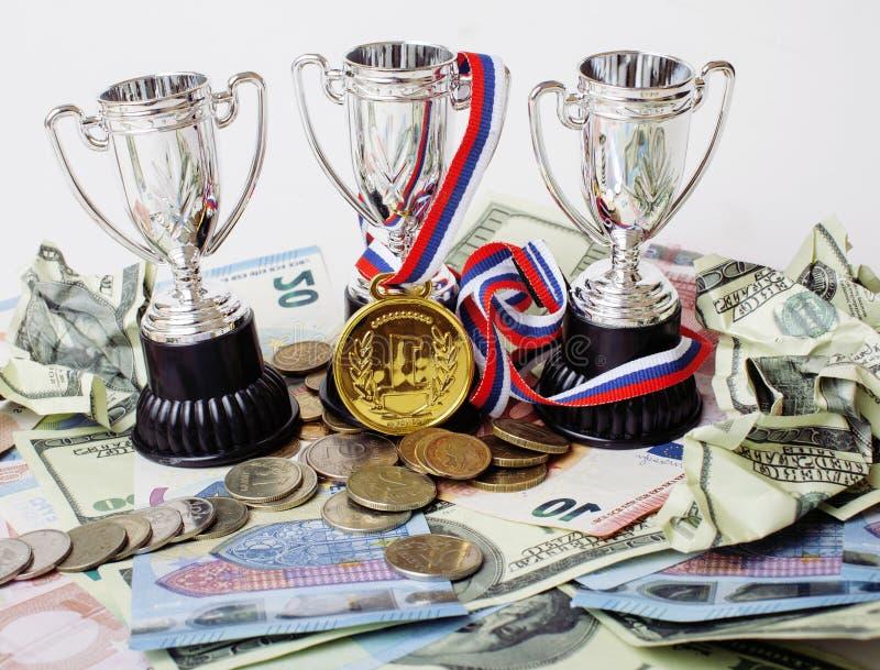 Vinnande begrepp för sport: tre koppar bland olika valutor euroet, dollaren, rubl, guldmedalj förlägger först royaltyfri fotografi