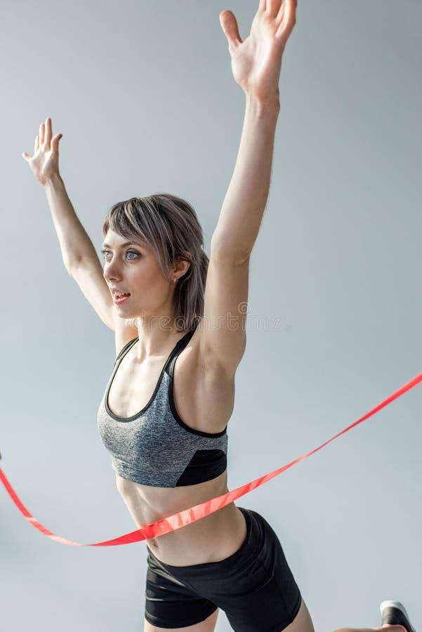 Vinnande loppkonkurrens för idrottskvinna och korsning mållinje royaltyfri foto