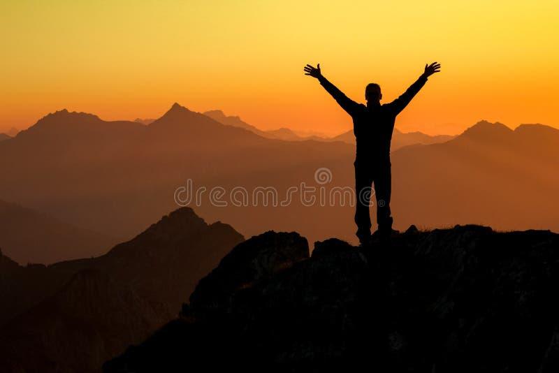 Vinnande man för lycklig framgång på toppmötearmar upp på solnedgången royaltyfria foton