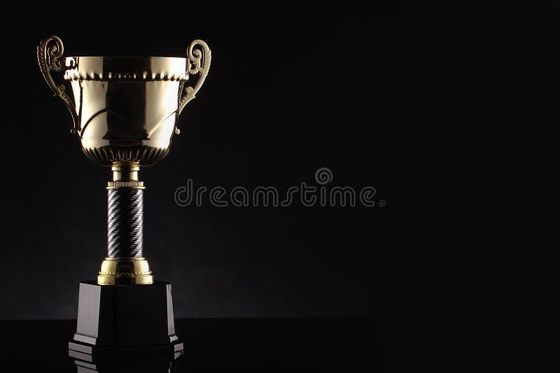 Vinnande trofé för stor utmärkelse i svart bakgrund royaltyfri foto