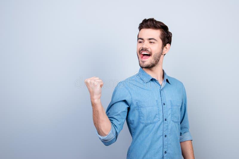 Vinnare! Den unga stiliga mannen firar seger Han lyfter royaltyfri bild