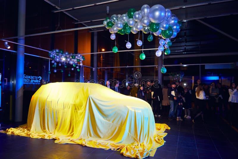 Vinnitsa, de Oekraïne - Maart 21, 2018 Renault Kadjar onder gele dekking wordt verborgen - nieuwe modelautopresentatie in toonzaa stock afbeelding