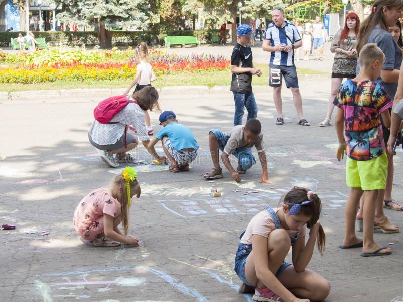 Vinnitsa, Oekraïne 24-08-2019 Kinderen trekken op de stoep met krijt royalty-vrije stock fotografie
