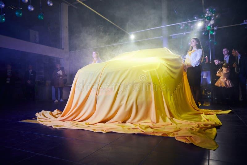 Vinnitsa, Ucrânia - 21 de março de 2018 Renault Kadjar escondido sob a tampa amarela - apresentação nova do carro modelo na sala  imagem de stock