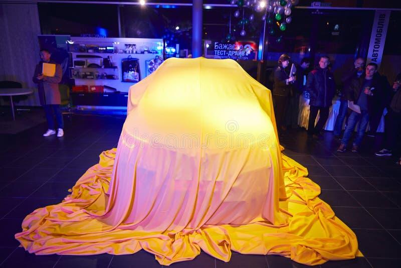 Vinnitsa, Ucrânia - 21 de março de 2018 Renault Kadjar escondido sob a tampa amarela - apresentação nova do carro modelo na sala  imagens de stock royalty free