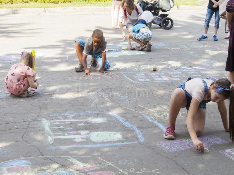 Vinnitsa, Ukraine. 08/24/2019. Children draw on the pavement with chalk. Vinnitsa, Ukraine. 08/24/2019. Boys and girls draw drawings with chalk on the pavement stock image