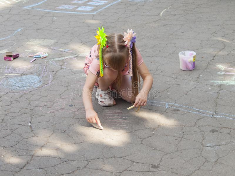 Vinnitsa, Ukraine. 08/24/2019. Children draw on the pavement with chalk. Vinnitsa, Ukraine. 08/24/2019. Girl draws with chalk on the pavement drawings royalty free stock photography
