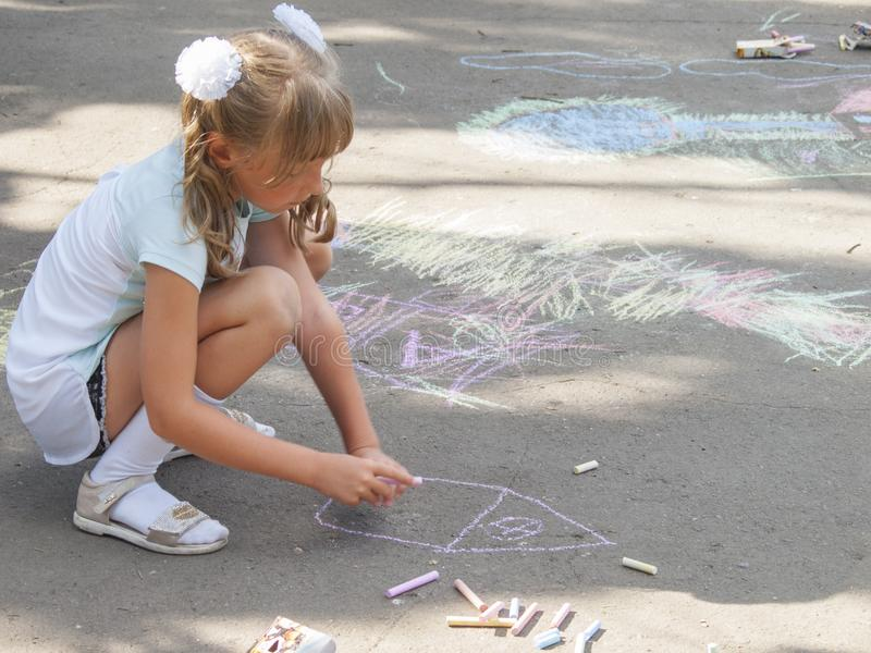 Vinnitsa, Ukraine. 08/24/2019. Children draw on the pavement with chalk. Vinnitsa, Ukraine. 08/24/2019. Girl draws with chalk on the pavement drawings stock image