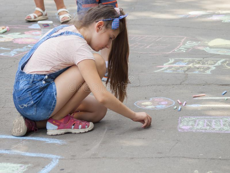 Vinnitsa, Ukraine. 08/24/2019. Children draw on the pavement with chalk. Vinnitsa, Ukraine. 08/24/2019. Girl draws with chalk on the pavement drawings royalty free stock photo