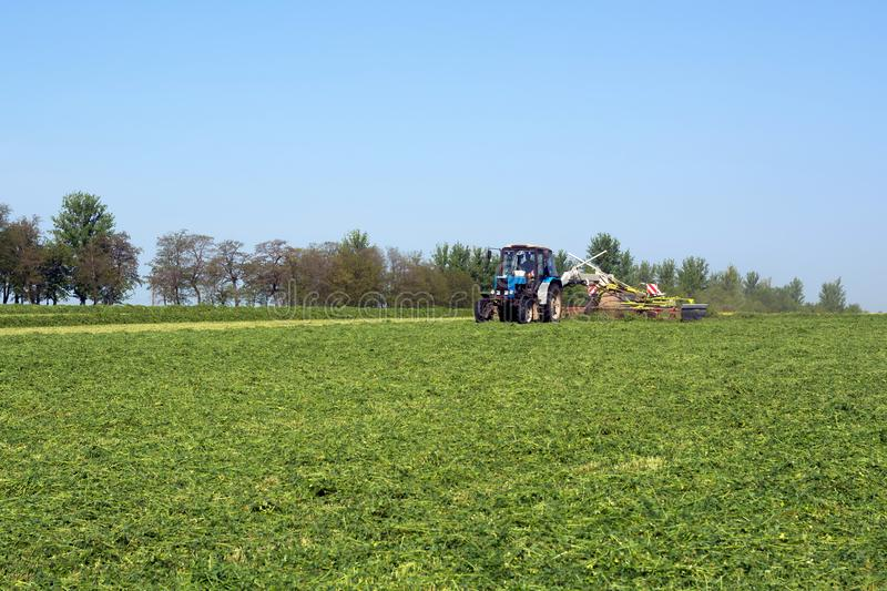 Vinnitsa/Ukraine - 05/04/2018: Tractor with the unit rides around the field and collects the felling of green fodder royalty free stock photography