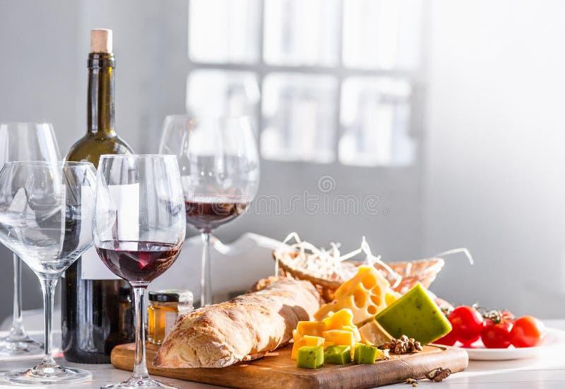 Vino, baguette e formaggio su fondo di legno immagine stock