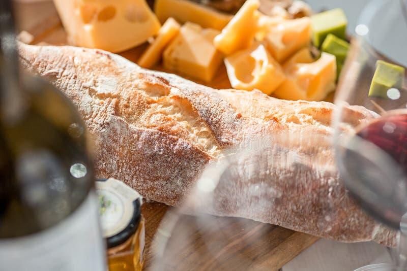 Vino, baguette e formaggio su fondo di legno fotografia stock