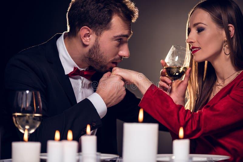 vino bevente della donna mentre uomo che bacia la sua mano alla data romantica immagine stock libera da diritti