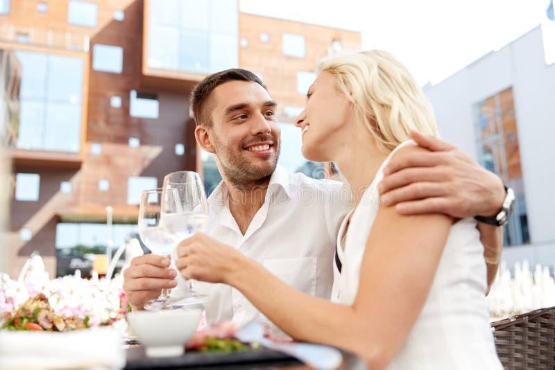 Vino bevente delle coppie felici al ristorante all'aperto immagini stock libere da diritti
