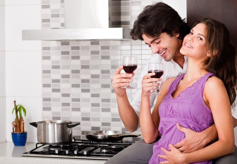 Vino bevente delle coppie nella loro cucina fotografia stock libera da diritti