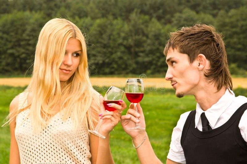Vino bevente delle giovani coppie all'aperto fotografia stock
