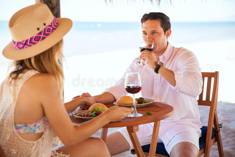 Vino bevente delle giovani coppie alla spiaggia immagine stock