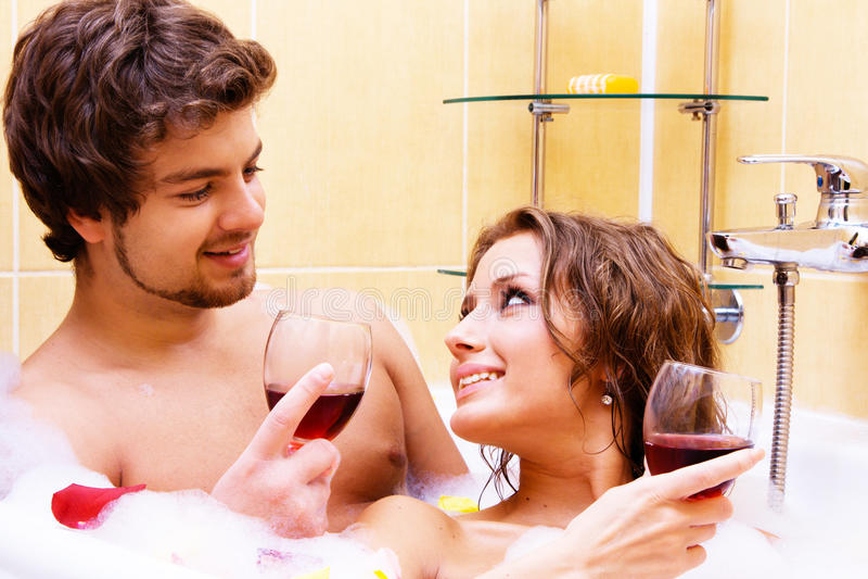 Vino bevente delle giovani coppie nel bagno fotografia stock