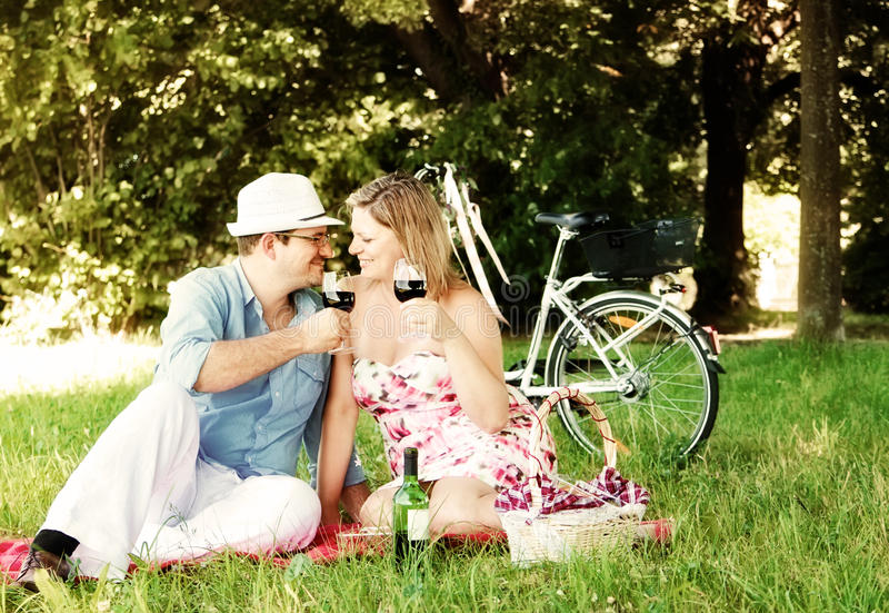 Vino bevente e sguardo delle coppie felici a vicenda immagini stock libere da diritti
