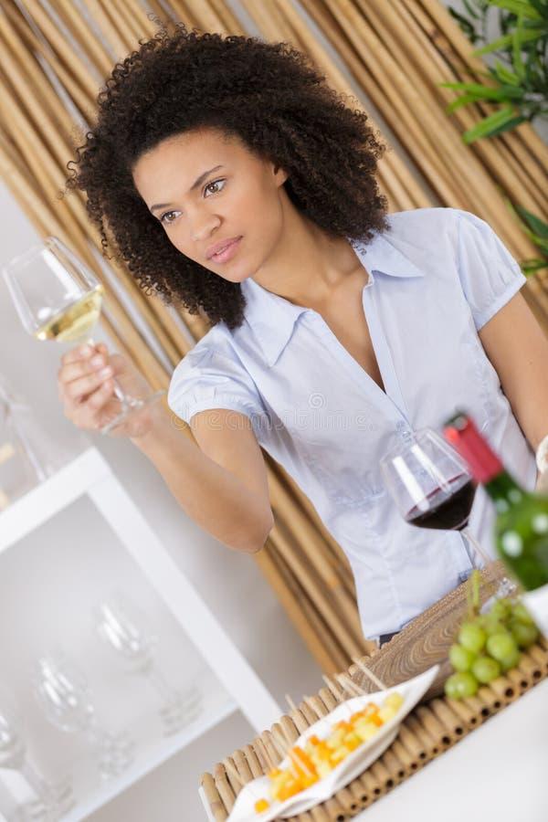 Vino bianco bevente castana attraente allegro in salone fotografie stock