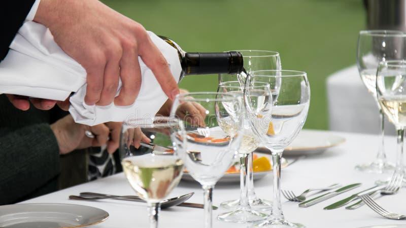 Vino bianco che versa nel vetro fotografia stock