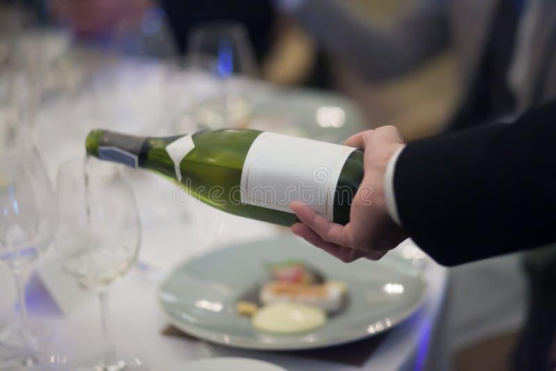 Vino bianco di versamento del cameriere nel vetro di vino in ristorante immagini stock libere da diritti