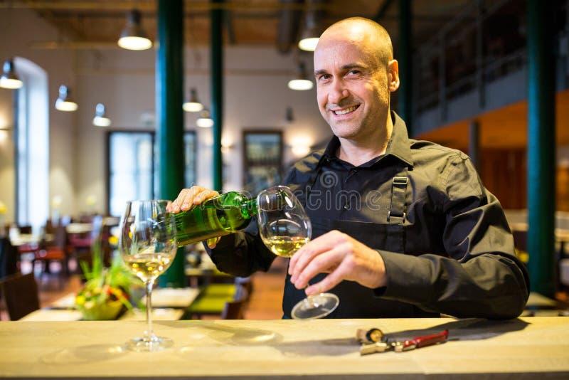 Vino bianco di versamento del cameriere in vetro immagini stock libere da diritti