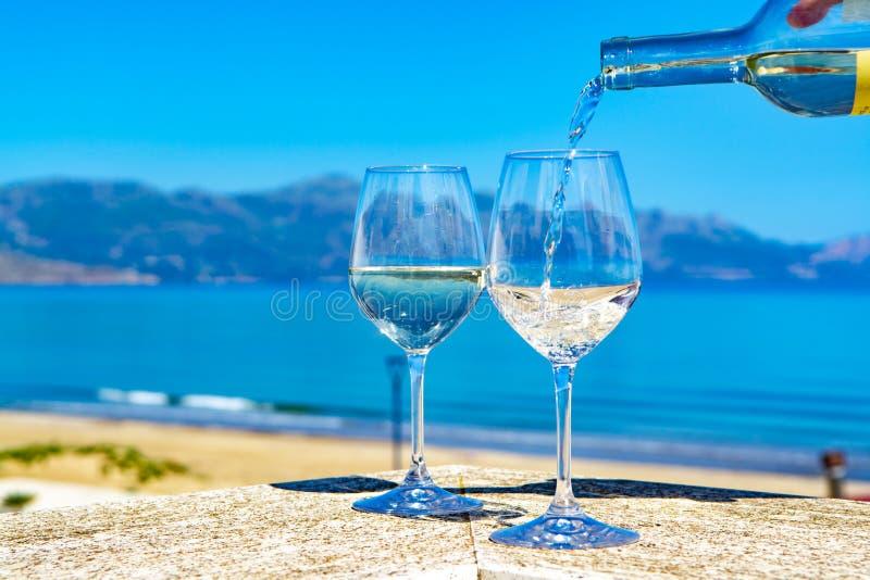 Vino blanco de colada del camarero en copas de vino en el mar azul del witn al aire libre de la terraza y Mountain View sobre fon fotografía de archivo libre de regalías