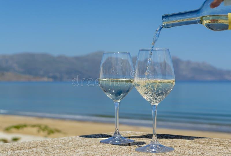 Vino blanco de colada del camarero en copas de vino en el mar azul del witn al aire libre de la terraza y Mountain View sobre fon imagen de archivo libre de regalías