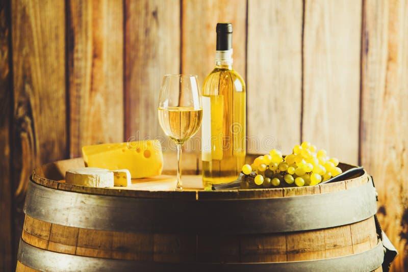 Vino blanco en barril con la uva y el queso en fondo de la pared de madera fotos de archivo