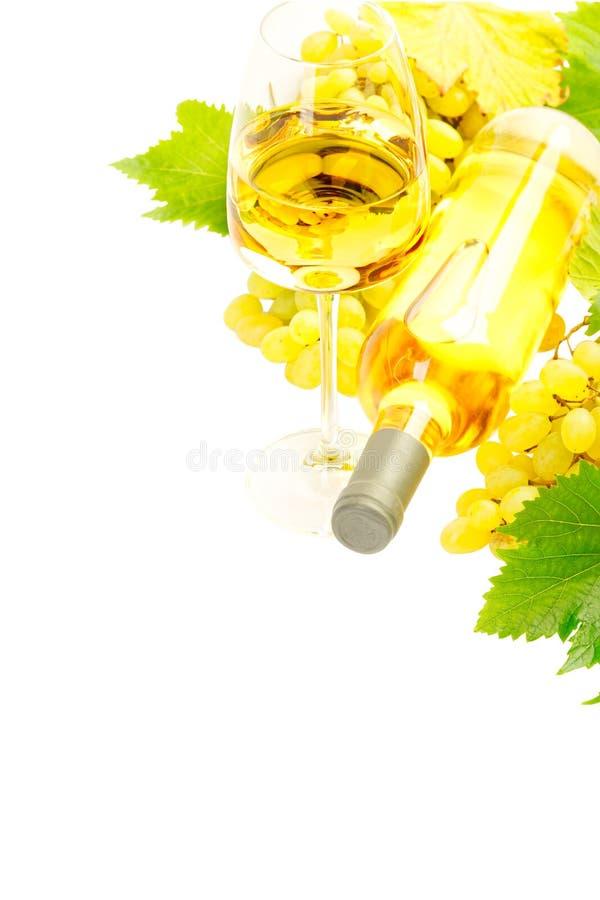 Vino blanco en botella y vidrio y un manojo de isola de las uvas blancas fotografía de archivo libre de regalías