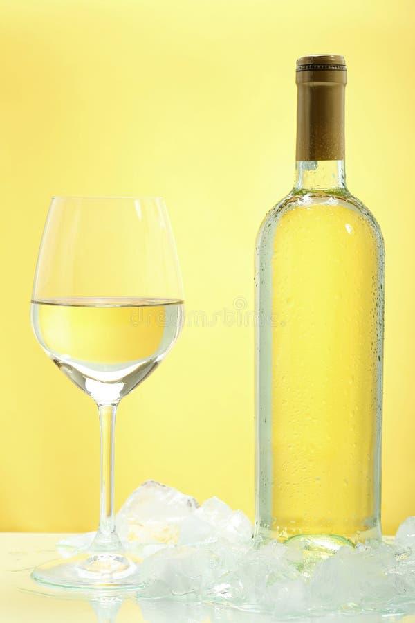 Vino blanco en vidrio en fondo amarillo foto de archivo