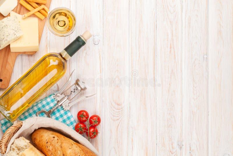 Vino blanco, queso y pan en el fondo de madera blanco de la tabla fotografía de archivo libre de regalías