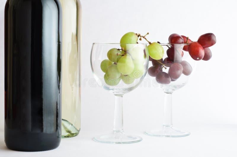 Vino blanco rojo y con las uvas fotografía de archivo