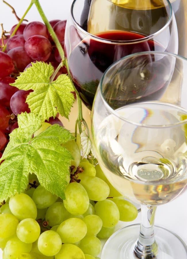 Vino blanco rojo y, con los manojos de uvas foto de archivo