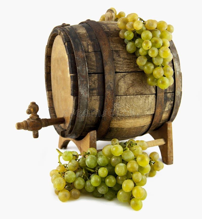 Vino blanco, uvas y barril viejo en el backgro blanco imagenes de archivo