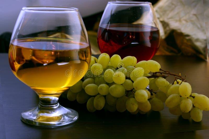 Vino blanco y rojo en el vidrio en la tabla con las uvas fotos de archivo