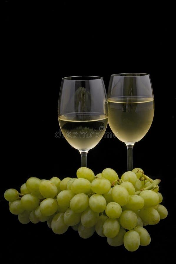 Vino blanco y uvas en negro imagen de archivo