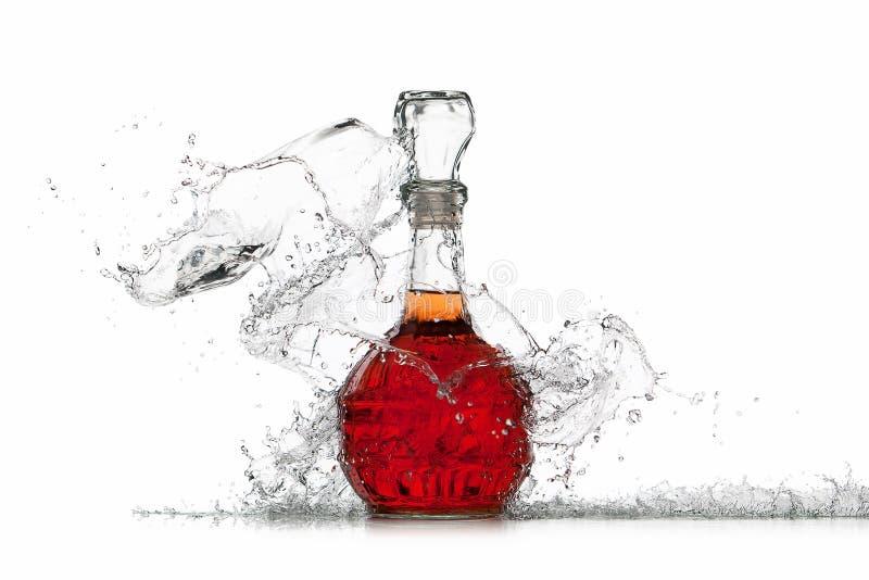 Vino Botella de vino rojo con el chapoteo del agua en el fondo blanco foto de archivo libre de regalías