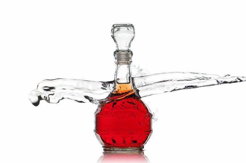 Vino Botella de vino rojo con el chapoteo del agua en el fondo blanco imagen de archivo libre de regalías