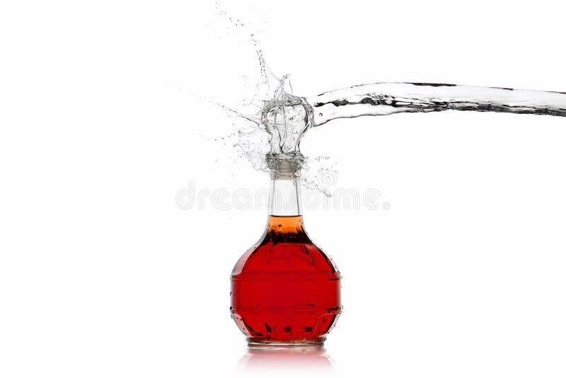 Vino Botella de vino rojo con el chapoteo del agua en el fondo blanco fotos de archivo libres de regalías