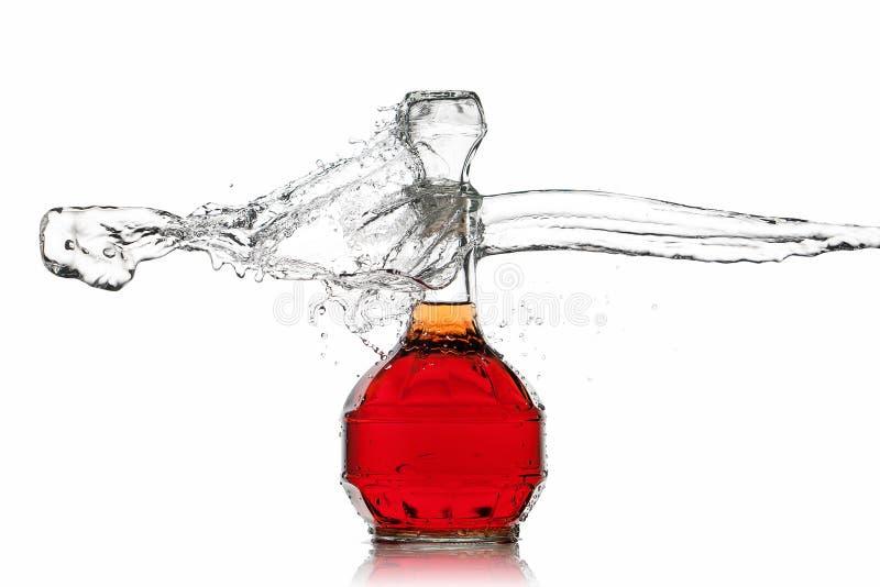 Vino Botella de vino rojo con el chapoteo del agua en el fondo blanco imágenes de archivo libres de regalías