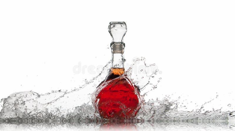 Vino Botella de vino rojo con el chapoteo del agua en el fondo blanco imagen de archivo
