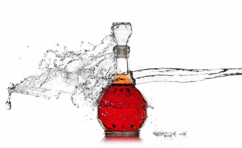 Vino Botella de vino rojo con el chapoteo del agua en el fondo blanco fotos de archivo