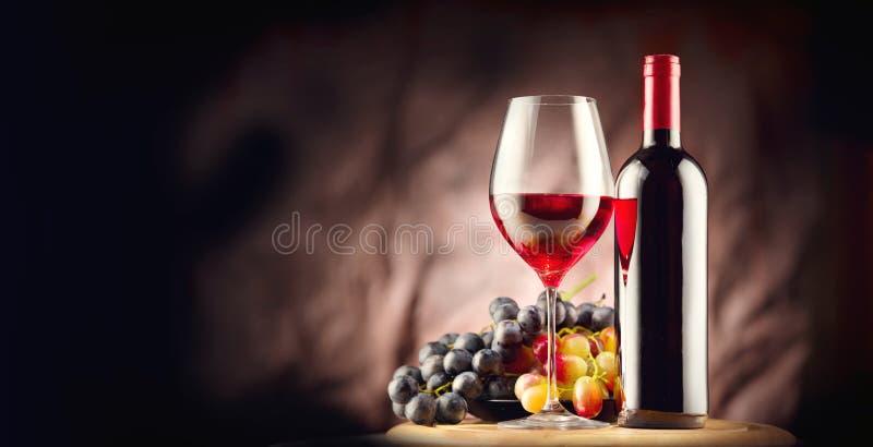 Vino Botella y vidrio de vino rojo con las uvas maduras fotografía de archivo libre de regalías