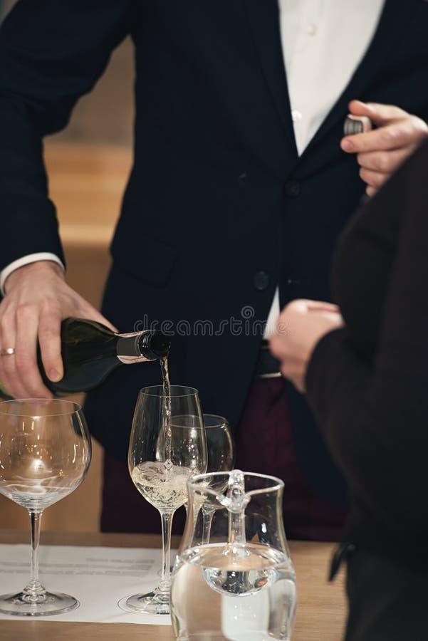Vino de colada del Sommelier en el vidrio en la degustación de vinos imágenes de archivo libres de regalías