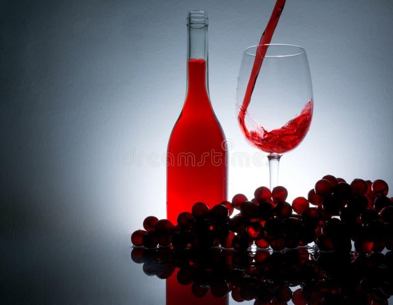 Vino de colada en un vidrio al lado de una botella de vino y de uvas fotos de archivo libres de regalías