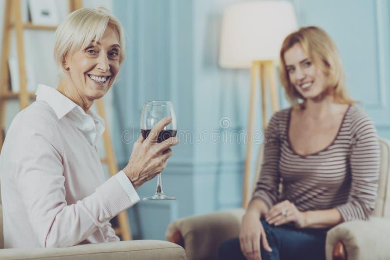 Vino de consumición de la mujer mayor en compañía de la hija imágenes de archivo libres de regalías