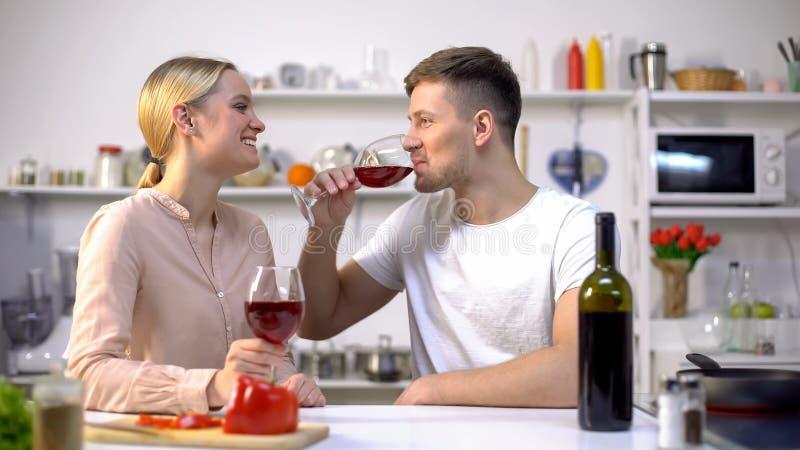 Vino de consumición de los pares jovenes en cocina, charlando y relajándose junto, romance fotos de archivo libres de regalías