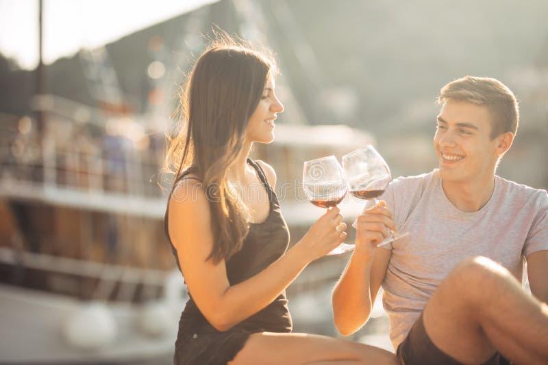 Vino de consumición de los pares románticos en la puesta del sol romance Dos personas que tienen una tarde romántica con un vidri imagenes de archivo